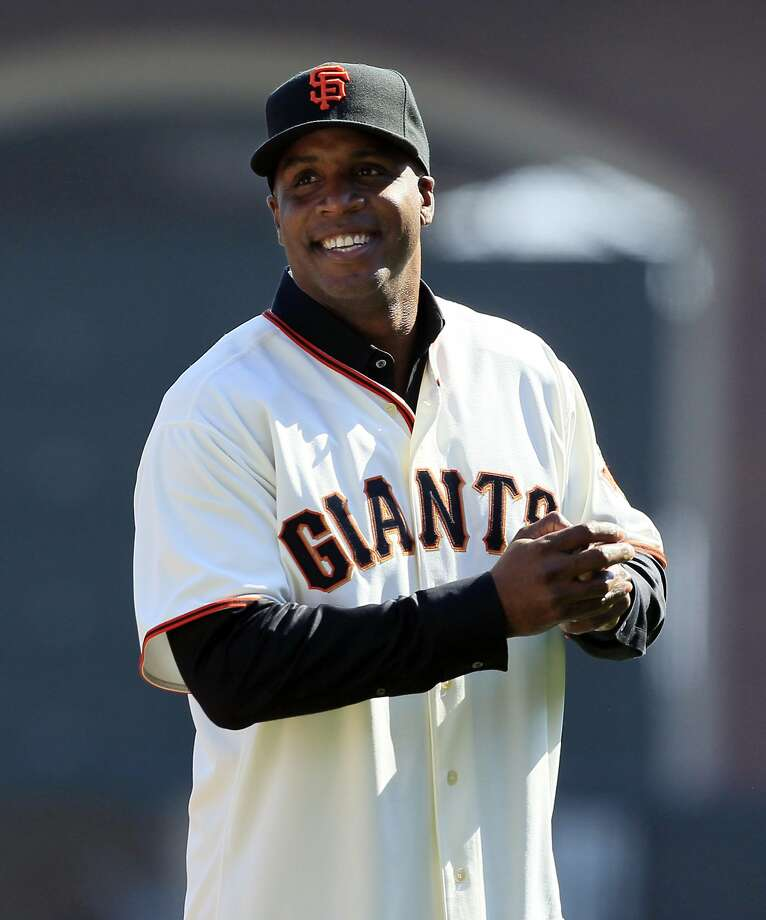 FILE - This Oct. 19, 2010, file photo shows former San Francisco Giants Barry Bonds acknowledging the crowd before throwing out a ceremonial first pitch before Game 3 of baseball's National League Championship Series against the Philadelphia Phillies, in San Francisco. Bonds is returning to the Giants as a spring training instructor. The Giants say Bonds is expected to arrive during the second week of March 2014. (AP Photo/Jeff Chiu, File) Photo: Jeff Chiu, Associated Press