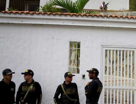 """Retired Venezuelan Army Gen. Angel Vivas, top right, stands armed inside his residence as military intelligence officers stand outside his home in Caracas, Venezuela, Sunday, Feb. 23, 2014. President Nicolas Maduro ordered on Saturday the arrest and investigation of the retired general for his statements on YouTube and Twitter. Maduro said Vivas is instigating violence at a time when two weeks of anti-government protests have left 10 dead and over 100 wounded. Vivas has been an opponent of the Venezuelan government since his 2007 resignation as director of the Ministry of Defense Engineering, due to the military's adoption of the slogan """"Fatherland, socialism or death, we shall overcome,"""" created in Cuba. Photo: Juan Manuel Hernandez, AP / AP"""