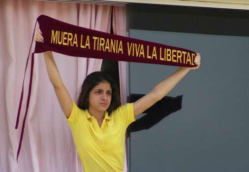 """Natalia Vivas, daughter of retired Army Gen. Angel Vivas, holds up a banner that reads in Spanish """"Death to tyranny, long live liberty"""" as members of military intelligence gather outside their home in an attempt to arrest her father in Caracas, Venezuela, Sunday, Feb. 23, 2014. President Nicolas Maduro ordered on Saturday the arrest and investigation of the retired general for his statements on YouTube and Twitter. Vivas, who is armed and holed up in his home, has been an opponent of the Venezuelan government since his 2007 resignation as director of the Ministry of Defense Engineering, due to the military's adoption of the slogan """"Fatherland, socialism or death, we shall overcome,"""" created in Cuba. Photo: Juan Manuel Hernandez, AP / AP"""