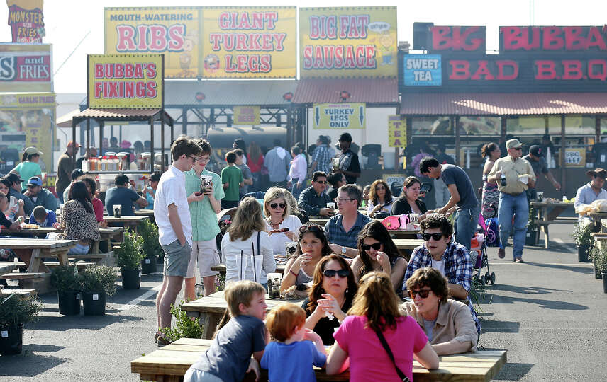 Enjoying the mild weather people eat in the food court during the San Antonio Stock Show & Rodeo Sun