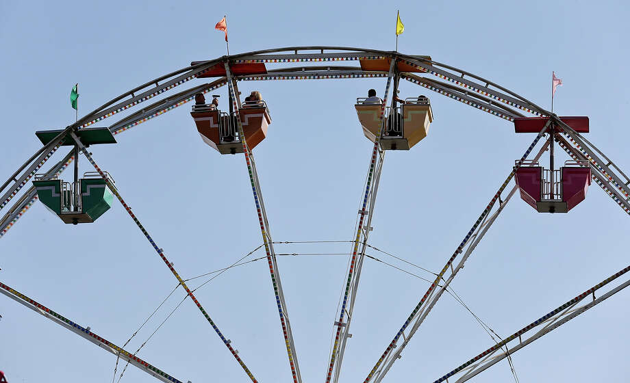 Enjoying the mild weather people ride the Mulligan Wheel at the Wade Shows Carnival during the San Antonio Stock Show & Rodeo Sunday Feb. 23, 2014. Photo: Edward A. Ornelas, San Antonio Express-News / © 2014 San Antonio Express-News