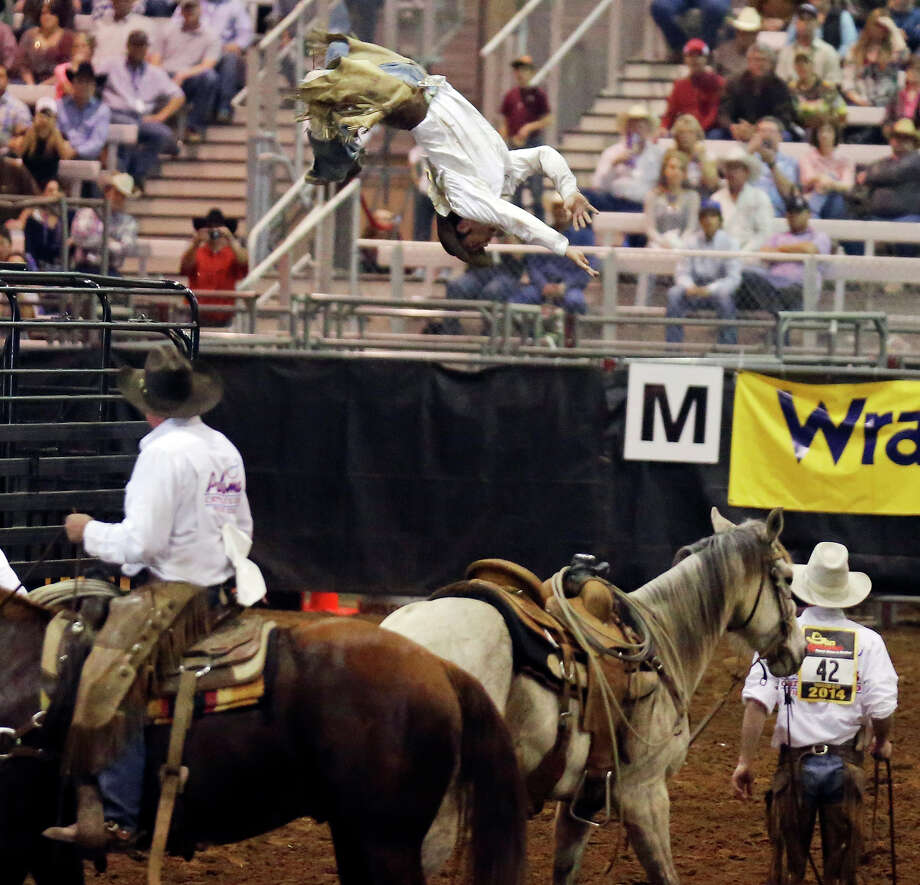 Paloma Cattle Co. team member Rowdy Yow (center) does a backflip off a trailer during the Ranch Rodeo Finals at the San Antonio Stock Show & Rodeo Sunday Feb. 23, 2014. Photo: Edward A. Ornelas, San Antonio Express-News / © 2014 San Antonio Express-News