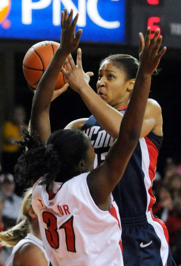 Connecticut's Maya Moore, right, shoots over Louisville's Asia Taylor during the first half of their NCAA college basketball game Sunday, Feb. 7, 2010, in Louisville, Ky. Connecticut defeated Louisville 84-38. (AP Photo/Timothy D. Easley) Photo: Timothy D. Easley, AP / AP2010