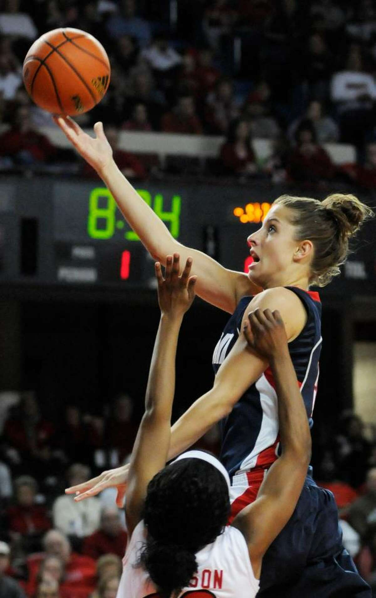 Connecticut's Caroline Doty, top, drives past the defense of Louisville's LaToya Johnson for a layup during the first half of their NCAA college basketball game Sunday, Feb. 7, 2010, in Louisville, Ky. Connecticut defeated Louisville 84-38. (AP Photo/Timothy D. Easley)
