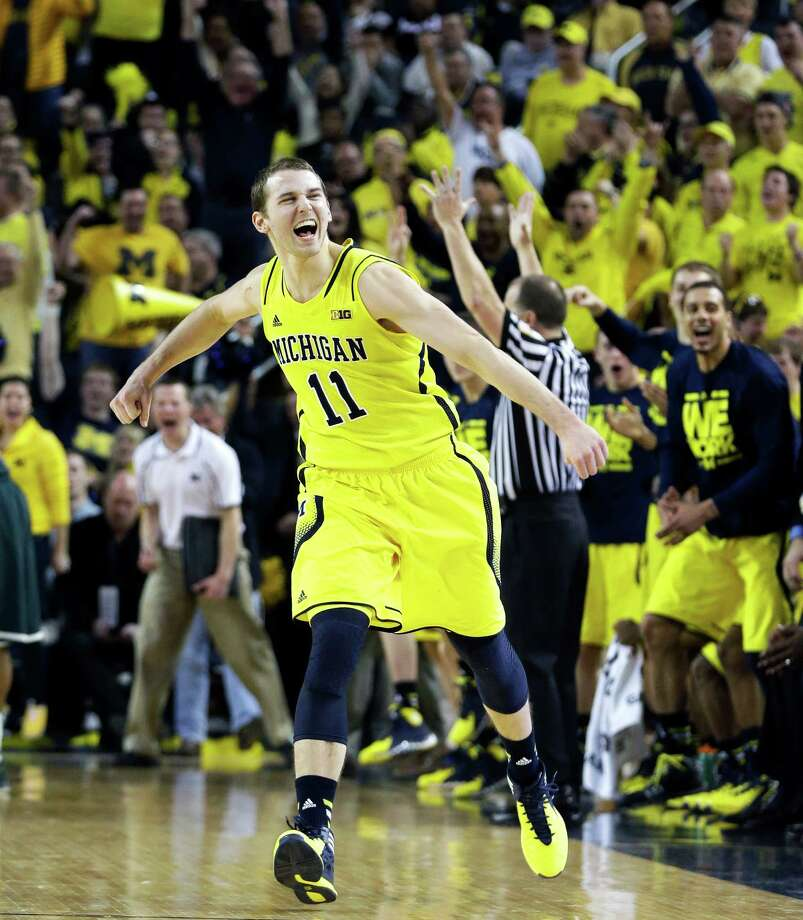 Michigan guard Nik Stauskas (11) reacts after making a three point basket during the second half of an NCAA college basketball game against Michigan State, Sunday, Feb. 23, 2014, in Ann Arbor, Mich. Michigan defeated Michigan State 79-70. (AP Photo/Carlos Osorio) ORG XMIT: AAS112 Photo: Carlos Osorio / AP