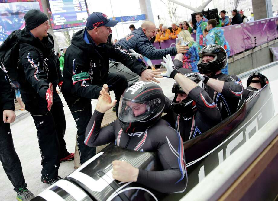 The team from the United States USA-1, with Steven Holcomb, Curtis Tomasevicz, Steven Langton and Christopher Fogt, celebrate after they won the bronze medal during the men's four-man bobsled competition final at the 2014 Winter Olympics, Sunday, Feb. 23, 2014, in Krasnaya Polyana, Russia. (AP Photo/Jae C. Hong) ORG XMIT: OLYBO223 Photo: Jae C. Hong / AP