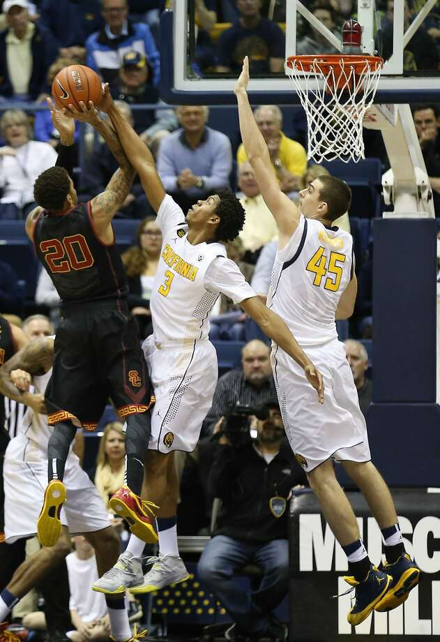 Tyrone Wallace and David Kravish reach high to defend a shot by USC guard J.T. Terrell. Photo: Kelley L Cox, Reuters
