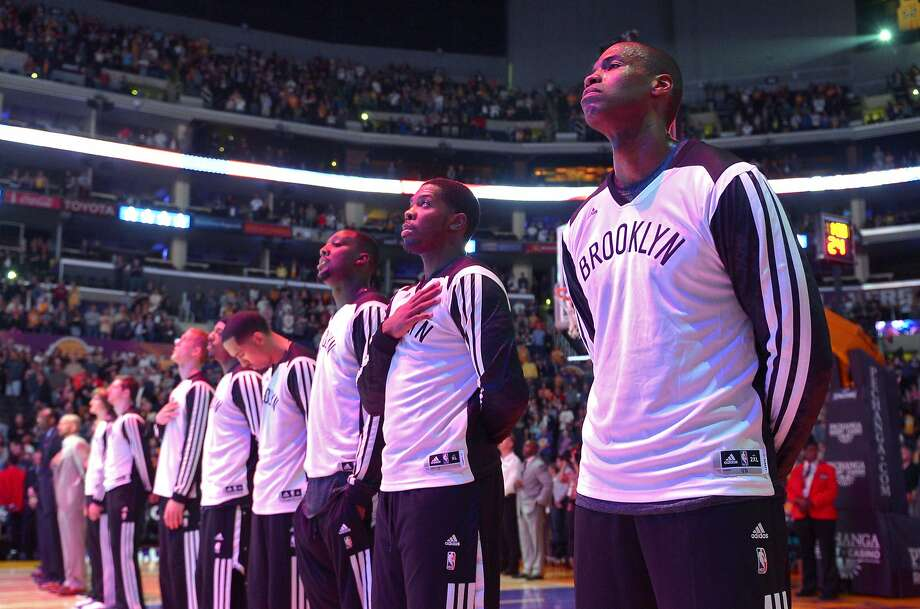 Jason Collins (right) stands with his Nets teammates during the national anthem at Staples Center. Photo: Mark J. Terrill, Associated Press