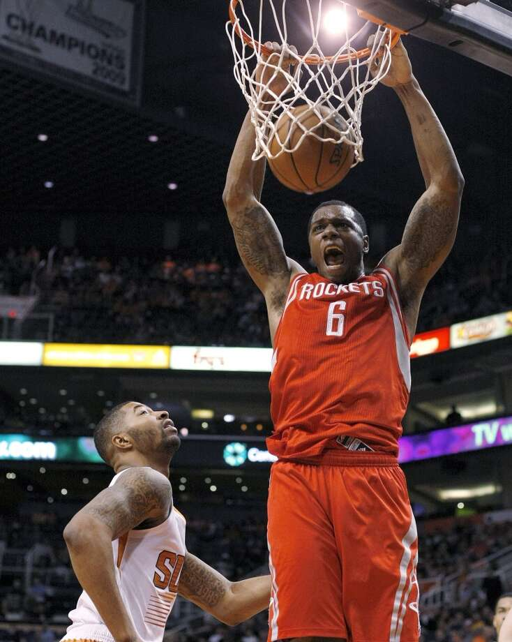 Rockets power forward Terrence Jones (6), right, dunks on Suns power forward Marcus Morris. Photo: Rick Scuteri, Associated Press