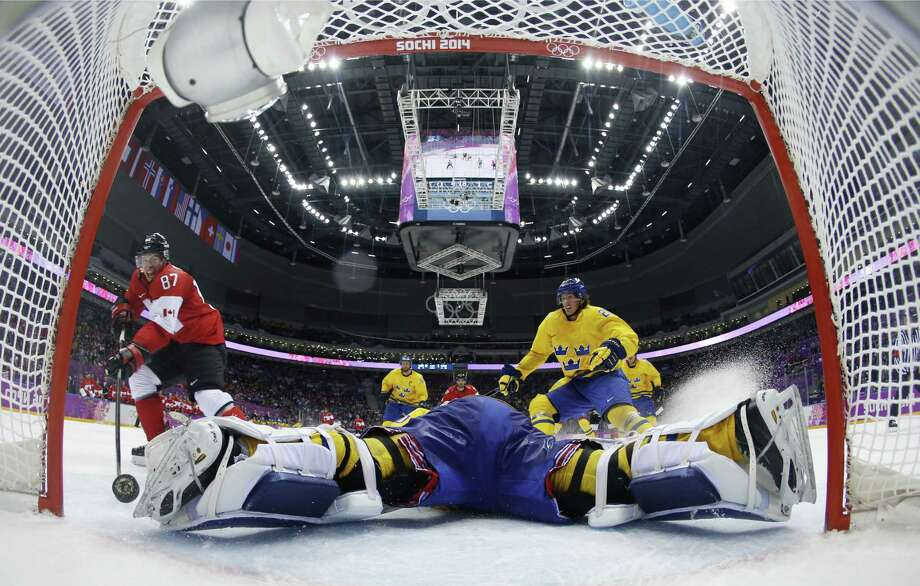 Canada forward Sidney Crosby scores a goal on an unassisted breakaway in the second period as Sweden's goaltender, Henrik Lundqvist, sprawls on the ice in a vain effort to stop him. Jonathan Toews and Chris Kunitz also scored for Canada. Photo: Julio Cortez / Associated Press / Pool AP
