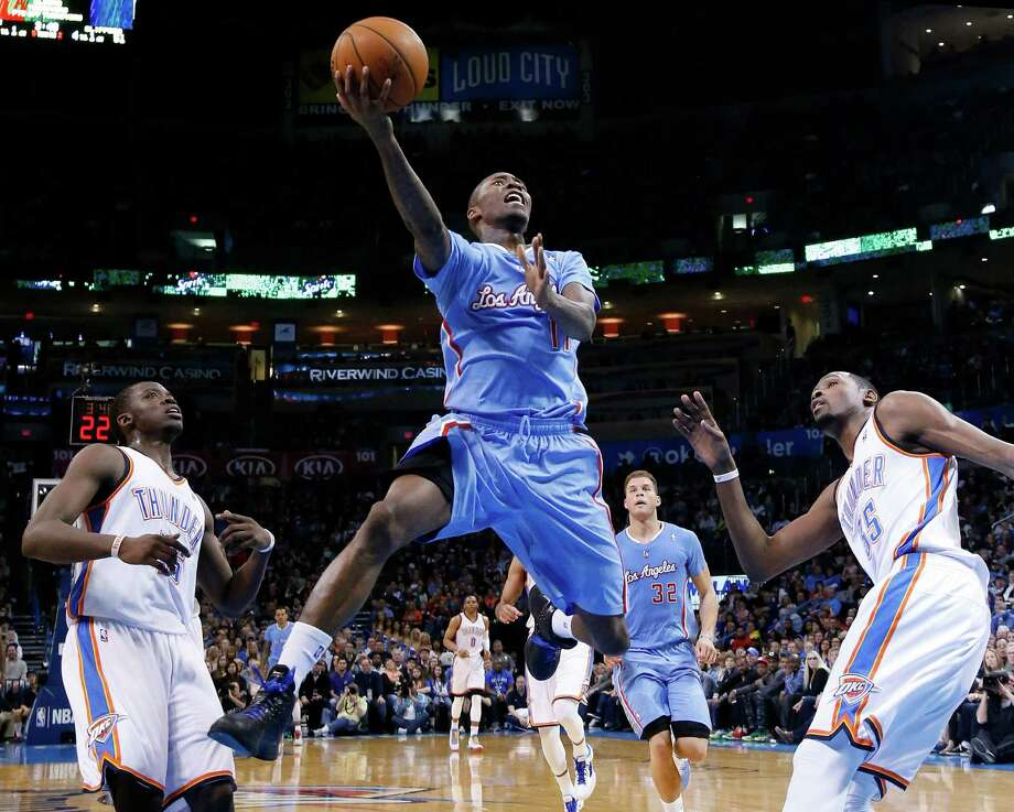 Los Angeles Clippers guard Jamal Crawford (11) goes up for a shot between Oklahoma City Thunder defenders Reggie Jackson (15) and Kevin Durant (35) in the second quarter of an NBA basketball game, Sunday, Feb. 23, 2014, in Oklahoma City. (AP Photo/Sue Ogrocki) ORG XMIT: OKSO104 Photo: Sue Ogrocki / AP