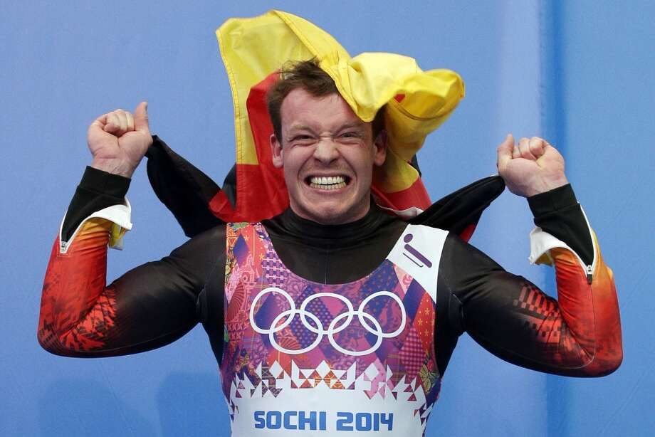 Felix Loch of Germany jumps onto the podium after he won the gold medal during the men's singles luge final at the 2014 Winter Olympics, Sunday, Feb. 9, 2014, in Krasnaya Polyana, Russia. Photo: Michael Sohn, Associated Press
