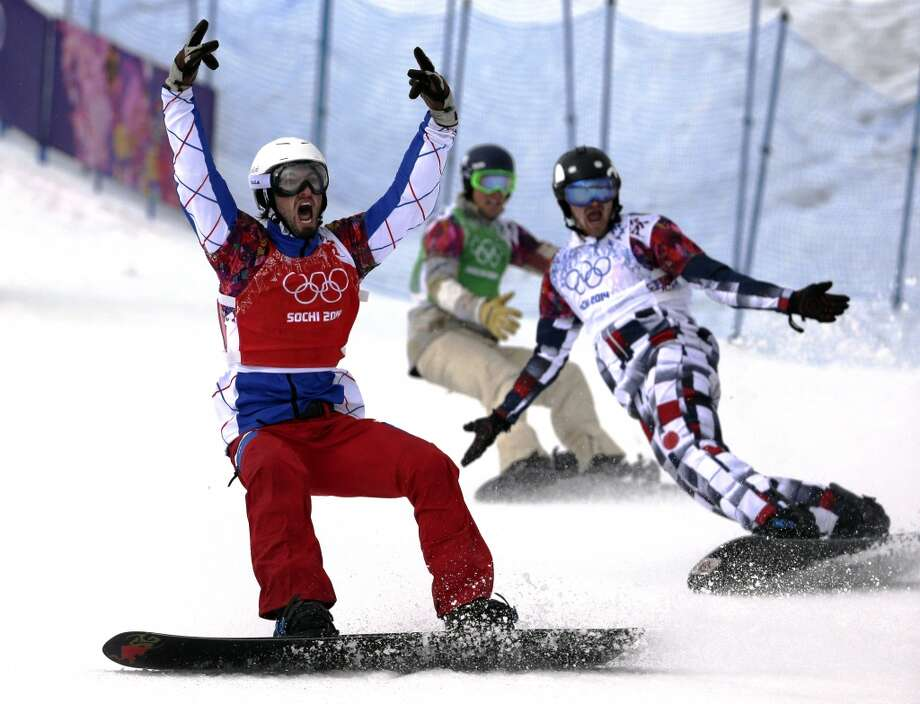 France's Pierre Vaultier, left, celebrates taking the gold medal ahead of silver medalist Nikolai Olyunin of Russia, right, and bronze medalist Alex Deibold of the United States in the men's snowboard cross final at the Rosa Khutor Extreme Park, at the 2014 Winter Olympics, Tuesday, Feb. 18, 2014, in Krasnaya Polyana, Russia. Photo: Andy Wong, Associated Press