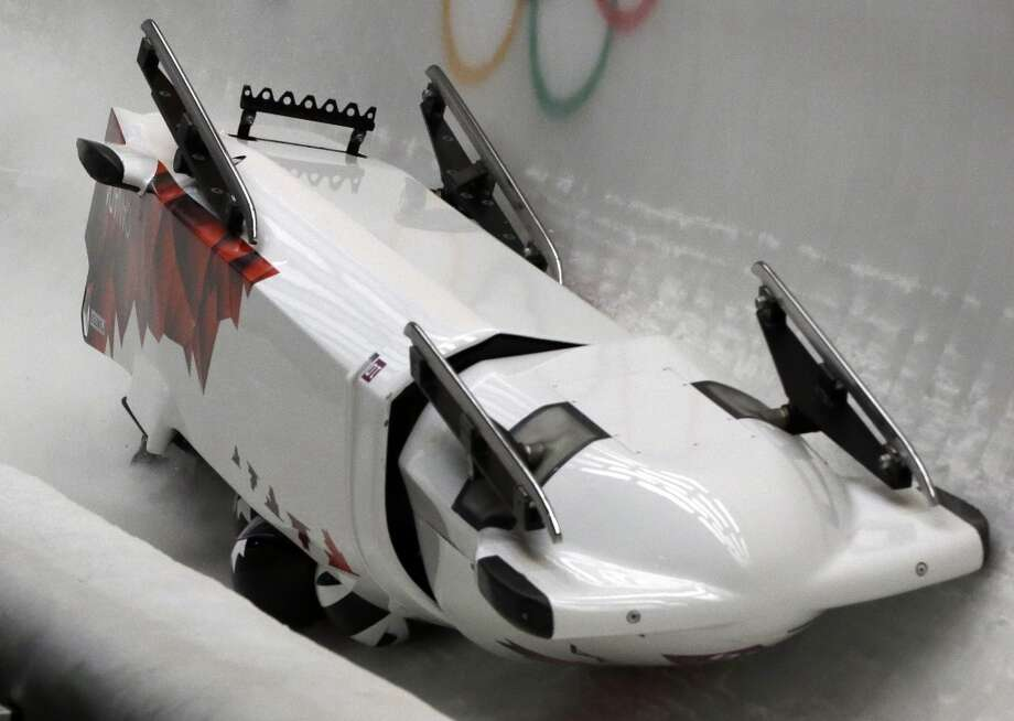 The team from Canada CAN-3, with Justin Kripps, Jesse Lumsden, Cody Sorensen and Ben Coakwell, slide down the track upside down after crashing in turn sixteen during the men's four-man bobsled competition at the 2014 Winter Olympics, Saturday, Feb. 22, 2014, in Krasnaya Polyana, Russia. Photo: Dita Alangkara, Associated Press