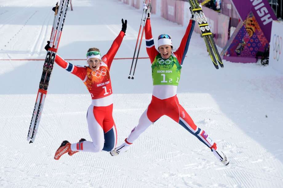 Norway's Ingvild Flugstad Oestberg and Norway's Marit Bjoergen celebrate after the Women's Cross-Country Skiing Team Sprint Classic Final at the Laura Cross-Country Ski and Biathlon Center during the Sochi Winter Olympics on February 19, 2014 in Rosa Khutor near Sochi. Photo: KIRILL KUDRYAVTSEV, AFP/Getty Images