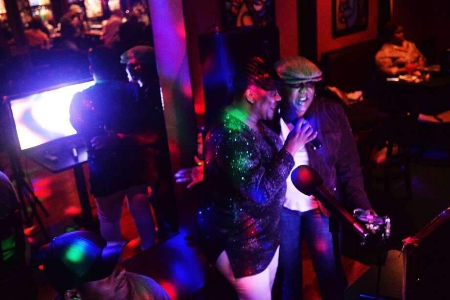 Wanda Reynaud, left, gets on the stage and karaoke with a friend during Karaoke night at Nell's place. Michael Rivera/ The Enterprise