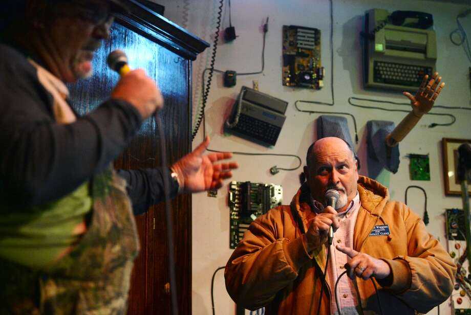"""David Smith, foreground, and Charlie Wiggins joke as they sing Jimmy Buffett's """"Margaritaville"""" on Tuesday night. Singers took the stage at Logon Cafe on Tuesday night for karaoke. Photo taken Tuesday, 2/11/14 Jake Daniels/@JakeD_in_SETX"""
