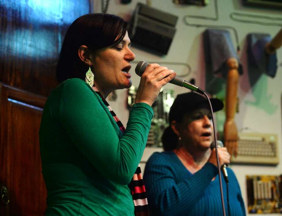 "Allison Ducote, front, and Angie Howard sing Bonnie Tyler's ""Total Eclipse of the Heart"" on Tuesday night. Singers took the stage at Logon Cafe on Tuesday night for karaoke. Photo taken Tuesday, 2/11/14 Jake Daniels/@JakeD_in_SETX"