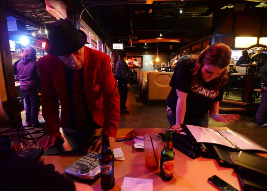 Tony Alamo, left, and Nikki Youngblood pick their songs for Wednesday night karaoke at Dylan's. Dylan's Bar and Grill in Port Arthur hosts karaoke on Wednesday nights. Photo taken Wednesday, 2/12/14 Jake Daniels/@JakeD_in_SETX