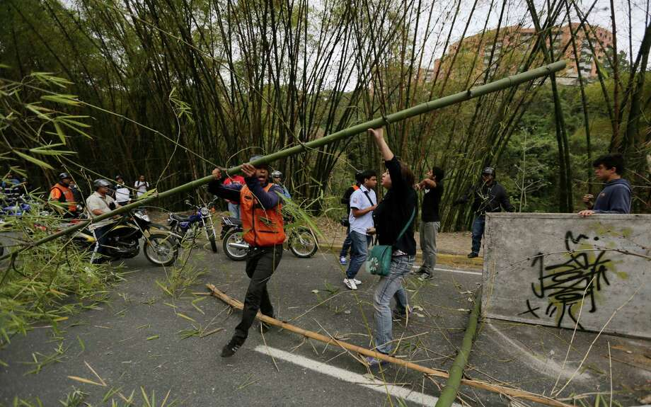 A motor cycle driver removes one of the bamboo stalks blocking the highway while a demonstrator tries to stop him from doing so, at El Cigarral neighborhood in Caracas, Venezuela, Monday, Feb. 24, 2014. Traffic has come to a halt in parts of the Venezuelan capital because of barricades set up by opposition protesters across major thoroughfares.The protests are part of a wave of anti-government demonstrations that have swept Venezuela since Feb. 12 and have resulted in at least 10 deaths. The protests in the capital Monday were peaceful. Police and National Guard troops stood by but did not act to remove the barricades despite the effect on the morning commute. Photo: Fernando Llano, AP / AP