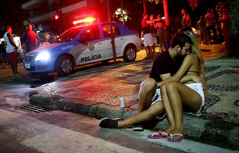 Put your hands where we can see them!Police arrive on the scene of a public display of affection in progress in Rio de Janeiro. After taking part in a pre-carnival bloco street celebration, these two held their own street party. Photo: Mario Tama, Getty Images,