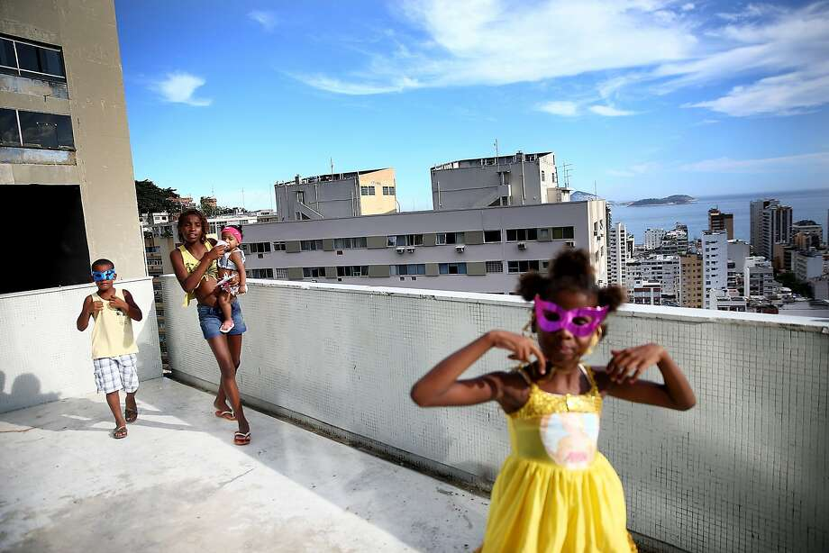 Revelers gather during pre-Carnival festivities in the Cantagalo shantytown community next to neighboring Pavao-Pavaozinho on February 22, 2014 in Rio de Janeiro, Brazil. The pacified favelas stand above Copacabana and Ipanema beaches. Ahead of the World Cup, some of Rio's pacified favelas have seen an increase in violence, including a number of shootings in Cantagalo and Pavao-Pavaozinho. Around 10,000 people live in the Cantagalo and Pavao-Pavaozinho communities with a total of 1.7 million Rio residents residing in shantytowns, many of which are controlled by drug traffickers. on February 22, 2014 in Rio de Janeiro, Brazil. Photo: Mario Tama, Getty Images,