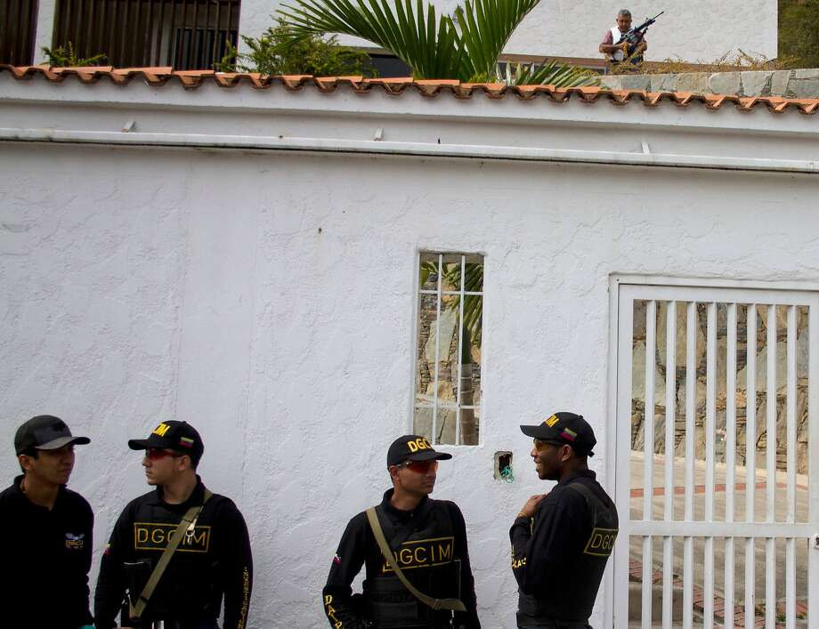 "Retired Venezuelan Army Gen. Angel Vivas, top right, stands armed inside his residence as military intelligence officers stand outside his home in Caracas, Venezuela, Sunday, Feb. 23, 2014. President Nicolas Maduro ordered on Saturday the arrest and investigation of the retired general for his statements on YouTube and Twitter. Maduro said Vivas is instigating violence at a time when two weeks of anti-government protests have left 10 dead and over 100 wounded. Vivas has been an opponent of the Venezuelan government since his 2007 resignation as director of the Ministry of Defense Engineering, due to the military's adoption of the slogan ""Fatherland, socialism or death, we shall overcome,"" created in Cuba.  Photo: Juan Manuel Hernandez, Associated Press"