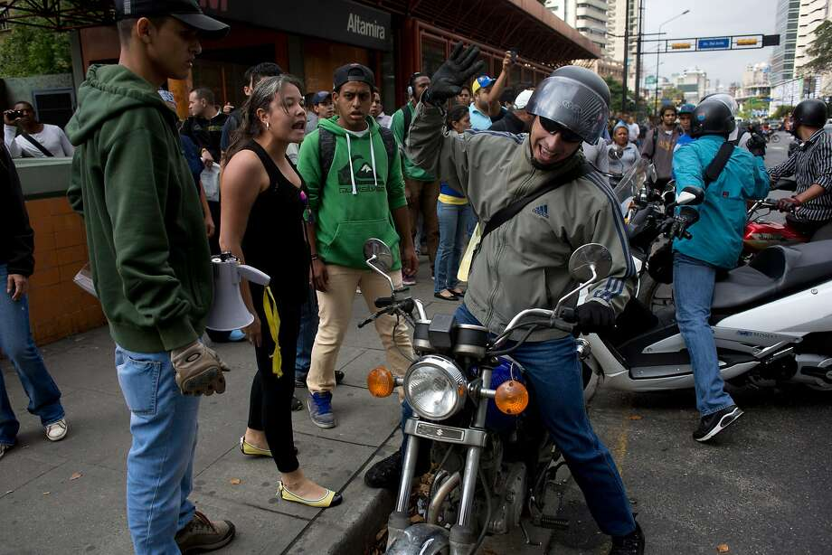 A motor cycle driver, right, argues with demonstrator that is blocking the highway at Altamira neighborhood in Caracas, Venezuela, Monday, Feb. 24, 2014. Traffic has come to a halt in parts of the Venezuelan capital because of barricades set up by opposition protesters across major thoroughfares. The protests are part of a wave of anti-government demonstrations that have swept Venezuela since Feb. 12 and have resulted in at least 10 deaths. The protests in the capital Monday were peaceful. Police and National Guard troops stood by but did not act to remove the barricades despite the effect on the morning commute. Photo: Rodrigo Abd, Associated Press