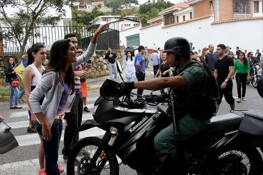 "Neighbors of retired Army Gen. Angel Vivas gather outside his home to try to stop security agents from arresting him in Caracas, Venezuela, Sunday, Feb. 23, 2014. President Nicolas Maduro ordered on Saturday the arrest and investigation of the retired general for his statements on YouTube and Twitter. Maduro said Vivas is instigating violence at a time when two weeks of anti-government protests have left 10 dead and over 100 wounded. Vivas has been an opponent of the Venezuelan government since his 2007 resignation as director of the Ministry of Defense Engineering, due to the military's adoption of the slogan ""Fatherland, socialism or death, we shall overcome,"" created in Cuba.  Photo: Juan Manuel Hernandez, Associated Press"