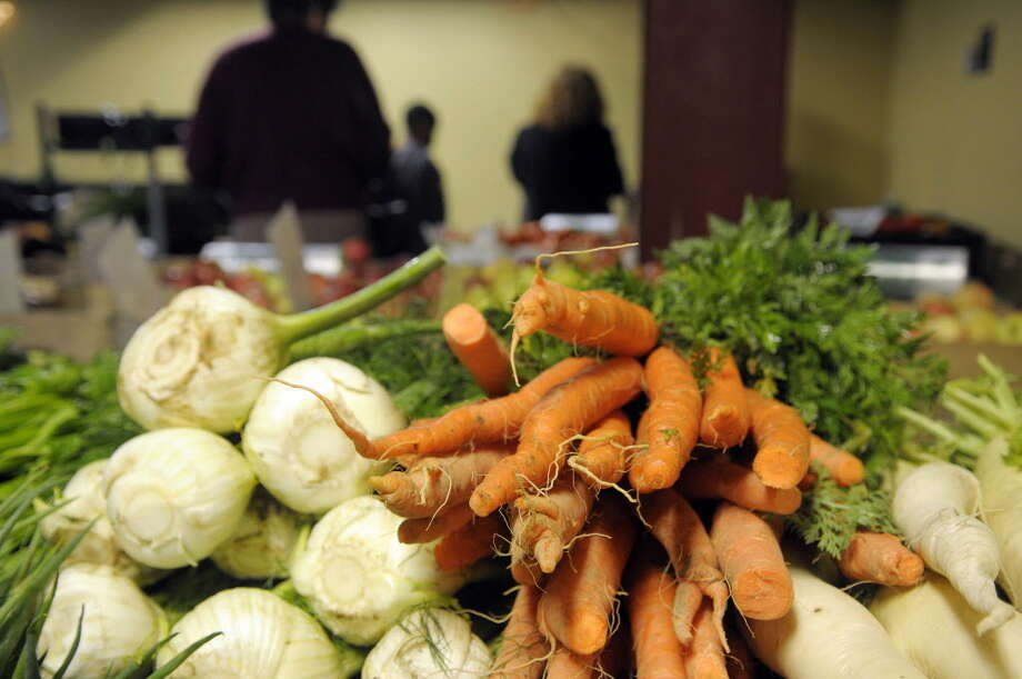 Carrots and other vegetables are stacked on a table for shoppers to buy  at the Schenectady Greenmarket inside Proctor's Theatre in Schenectady.   (Paul Buckowski / Times Union archive) Photo: Paul Buckowski / 00010916A