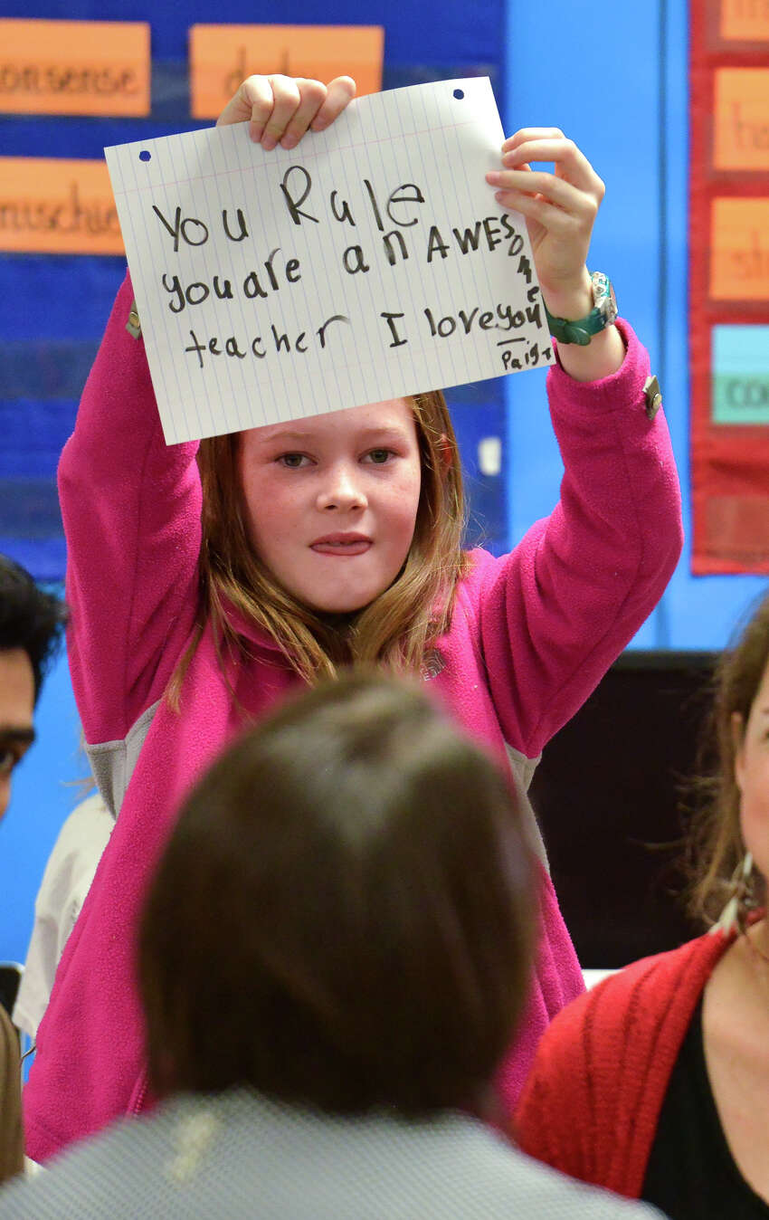 A student holds up a sign as Cambridge Elementary School third grade teacher Cheryl Duckers is congratulated by HEB Public Affairs during an HEB Excellence in Education Award surprise presentation Monday morning.