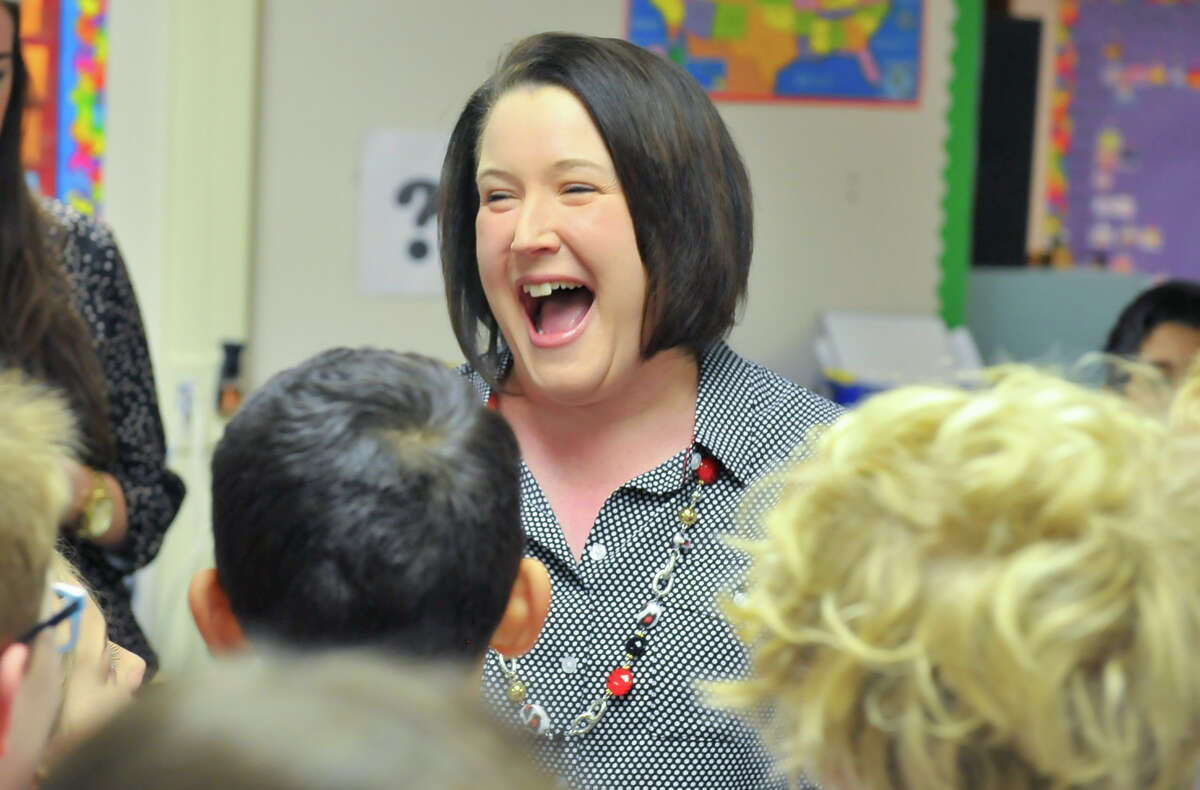 Cambridge Elementary School third grade teacher Cheryl Duckers (center) is all smiles shortly after being awarded a 2014 HEB Excellence in Education Award in a surprise presentation Monday morning.