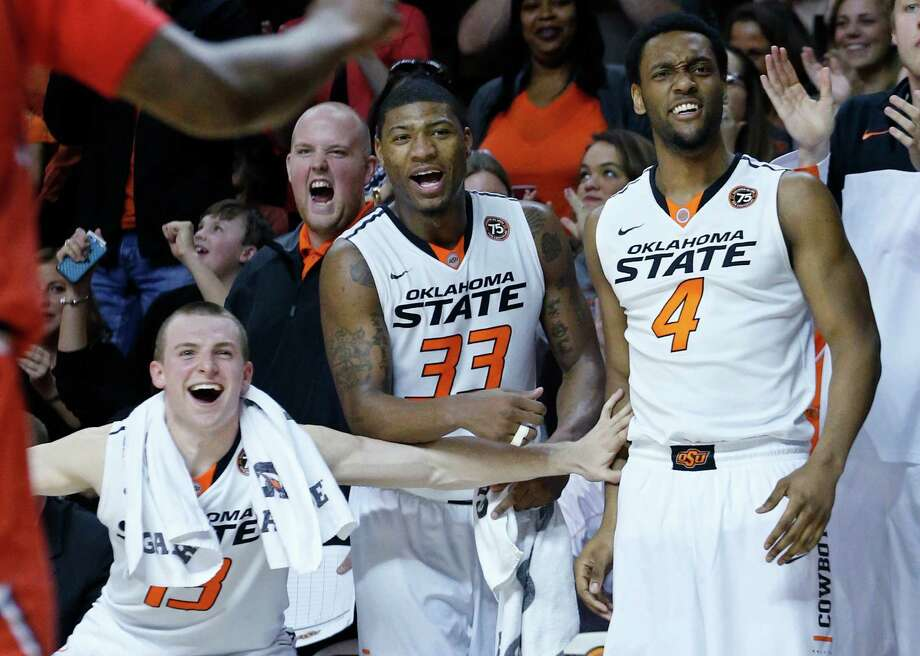 Oklahoma State guard Phil Forte (13), guard Marcus Smart (33) and wing Brian Williams (4) cheer on the bench following a dunk by teammate Le'Bryan Nash in the second half of an NCAA college basketball game against Texas Tech in Stillwater, Okla., Saturday, Feb. 22, 2014. Oklahoma State won 84-62. (AP Photo/Sue Ogrocki) Photo: Sue Ogrocki, Associated Press / AP