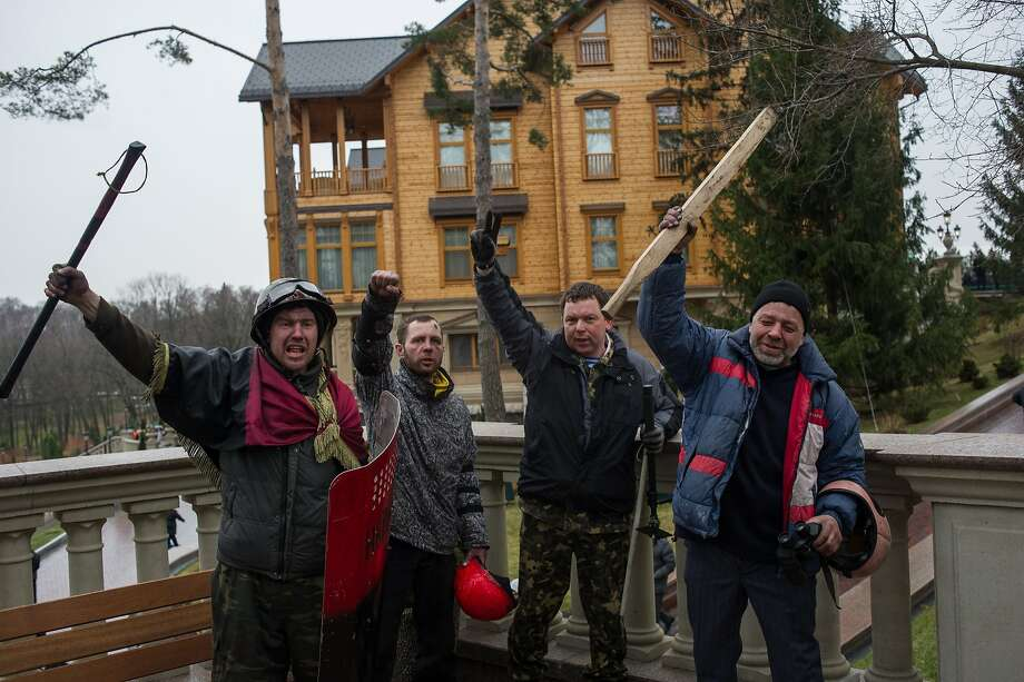 Protesters pose in front of Ukrainian ex-president Viktor Yanukovych's countryside residence in Mezhyhirya, Kiev's region, Ukraine, Saturday, Feb, 22, 2014. After months of anti-government protests, Yanukovych, now a fugitive, was impeached and his compound was opened to thousands of visitors. Ukrainian security and volunteers from among Independence Square protesters have joined forces to protect the presidential countryside retreat from vandalism and looting.  Photo: Andrew Lubimov, Associated Press