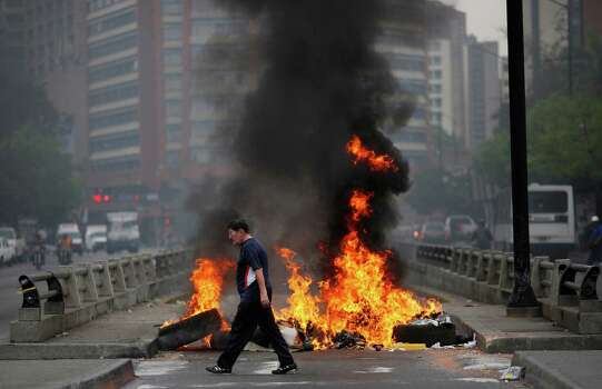 A pedestrian walks in front of a burning barricade blocking the highway in Chacao, Caracas, Venezuela, Monday, Feb. 24, 2014. Traffic has come to a halt in parts of the Venezuelan capital because of barricades set up by opposition protesters across major thoroughfares. The protests are part of a wave of anti-government demonstrations that have swept Venezuela since Feb. 12 and have resulted in at least 10 deaths. The protests in the capital Monday were peaceful. Police and National Guard troops stood by but did not act to remove the barricades despite the effect on the morning commute. Photo: Rodrigo Abd, AP / AP