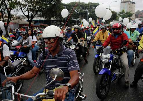 Motorcyclists attend a rally in support of Venezuela's President Nicolas Maduro in Caracas, Venezuela, Monday, Feb. 24, 2014. Opposition protesters erected barricades across major thoroughfares on Monday, bringing traffic to a halt in parts of the Venezuelan capital in a continuation of the unrest that has roiled the country for nearly two weeks. The demonstrators blame Maduro's administration for the country's high crime rate and economic troubles. Photo: Rodrigo Abd, AP / AP
