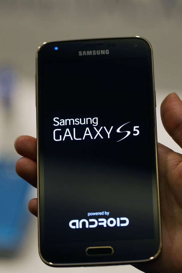 An employee displays a Galaxy S5 smartphone during a Samsung Electronics Co. news conference ahead of the Mobile World Congress in Barcelona, Spain, on Sunday, Feb. 23, 2014. Top telecommunication managers will rub shoulders in Barcelona next week at the Mobile World Congress, Monday, Feb. 24 - 27, a traditional venue for showcasing the latest products for dealmaking. Photographer: Angel Navarette/Bloomberg Photo: Angel Navarette, Bloomberg