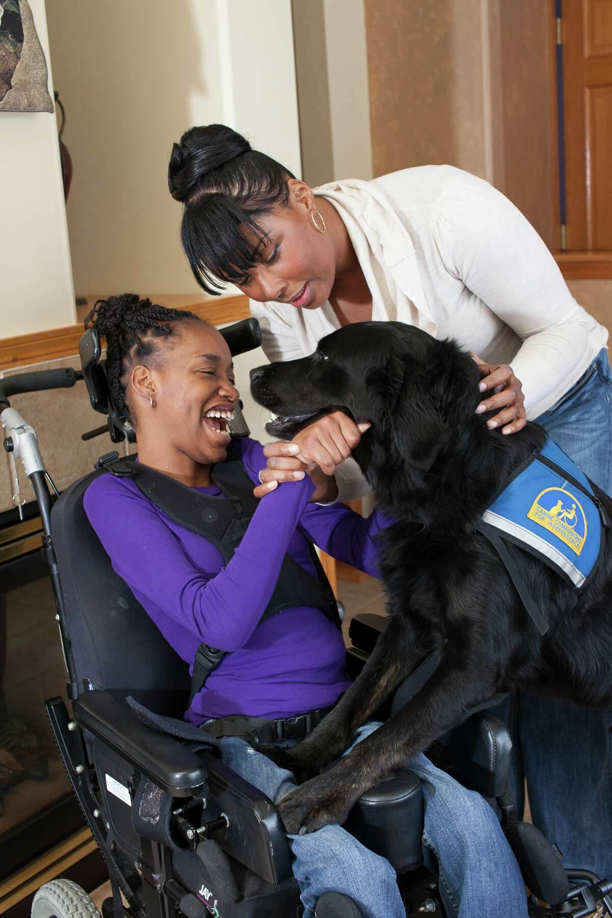 Canine Companions assistance dog Marco provides physical therapy to Barbara by getting her arms moving.