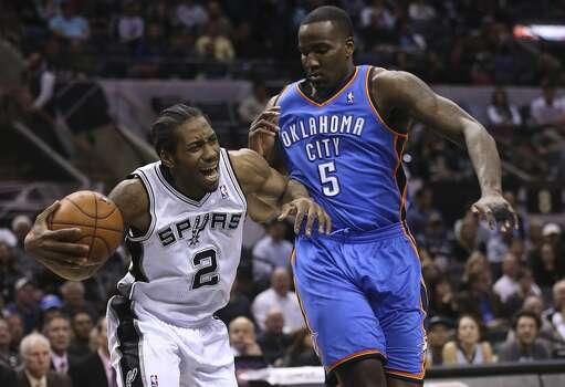 San Antonio Spurs' Kawhi Leonard tries to get around Oklahoma City Thunder's Kendrick Perkins during the first half at the AT&T Center, Wednesday, Jan. 22, 2014. Photo: Jerry Lara, San Antonio Express-News