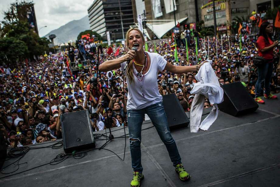 "Lilian Tintori, wife of jailed opposition leader Leopoldo Lopez, holds up a T-shirt with the slogan ""Who Tires Loses"" during a protest rally Saturday in Caracas, Saturday. Photo: Meridith Kohut / New York Times / 2013 Meridith Kohut"