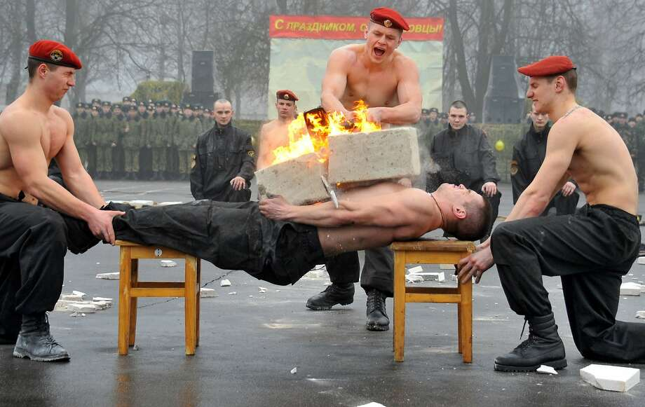 Belarus barbecue: Outside Minsk, an Interior Ministry special forces soldier demonstrates his ability to balance flaming cement blocks on his torso while planking between two chairs. Photo: Viktor Drachev, AFP/Getty Images