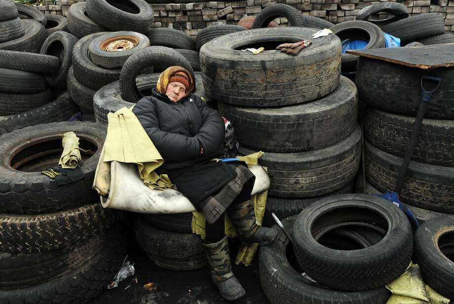 Extremely tire-d: A Ukrainian woman sleeps on a barricade in central Kiev. Parliament 