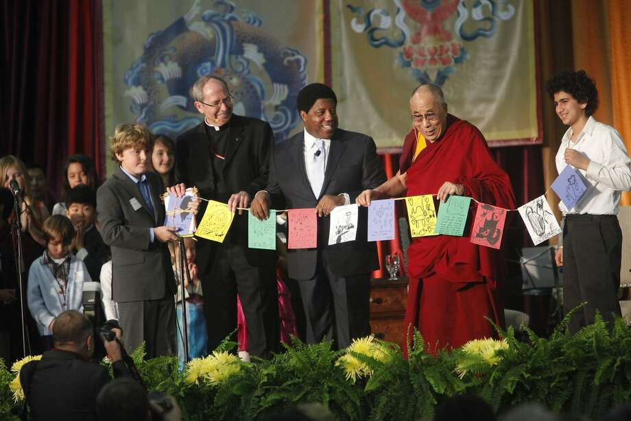 Students from Living Wisdom School in Palo Alto present a prayer flag to the Dalai Lama, who is joined onstage at Santa Clara University by university President Michael Engh (left) and Dignity Health CEO Lloyd Dean. Photo: Lea Suzuki, The Chronicle