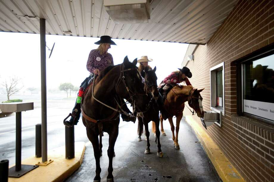 Tina Wargo, right, conducts business at the bank during a quick break from the trail ride, Monday, Feb. 24, 2014, in Alvin. Wargo, Judy Mitchell  and Noelle Hirst are with the Texas Independence Trail Ride on their way to Houston. Photo: Marie D. De Jesús, Houston Chronicle / © 2014 Houston Chronicle