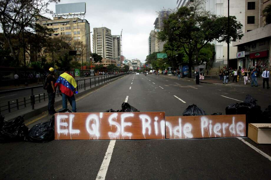 "People gather next to a barricade with a sign that reads in Spanish: ""He who gives up, loses""  in Caracas, Venezuela, Monday, Feb. 24, 2014. Since Feb. 12, opponents of President Nicolas Maduro have been staging countrywide protests that the government says have resulted in scores of deaths and more than one hundred injuries. The demonstrators blame Maduro's administration for the country's high crime rate and economic troubles. Photo: Rodrigo Abd, AP / AP"
