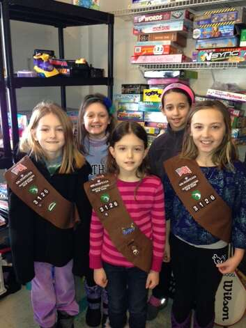 """Division Street Elementary School second-graders Theresa Prehn, Maggie Pendergast, Anna Sheinkin, Zoe Shapiro and Avery Stockamore, part of Brownie Troop 3126, make donations of clothing, household wares, games and books to Franklin Community Center to assist local children and families in need. The items were delivered by the troop to Franklin Community Center's """"Free Store"""" on 101 Washington St., Saratoga Springs. (Submitted photo)"""