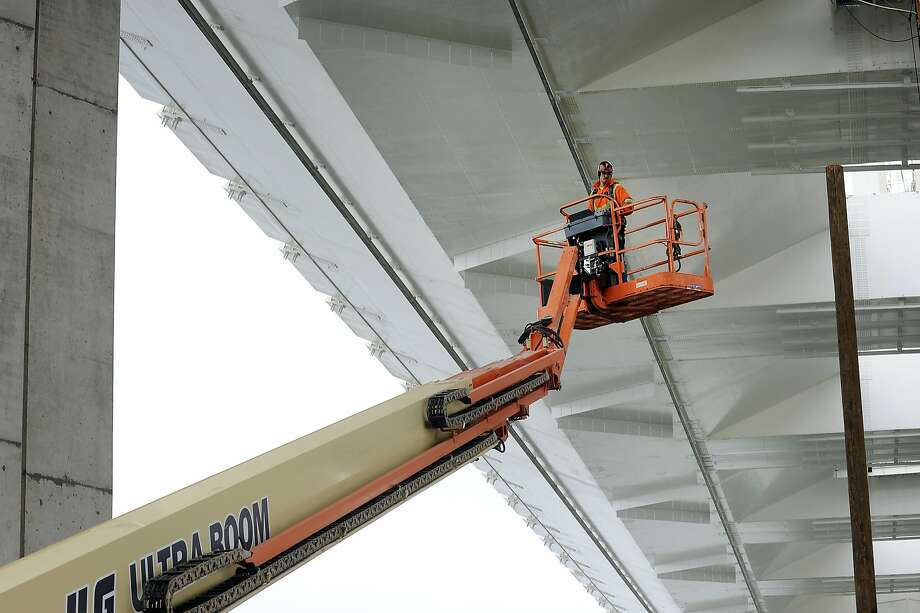 A worker uses a lift to reach the underside of the eastern span of the Bay Bridge this month. The bridge is designated as a structure that can carry emergency traffic within a day of a major earthquake, but welds are raising questions about its reliability. Photo: Michael Short, Special To The Chronicle