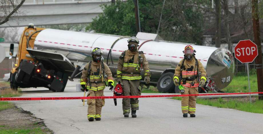 Houston Fire Department personnel work at scene where a tanker truck drove into a ditch at the corner of Des Chaumes and Roland St. near U.S.59 Monday, Feb. 24, 2014 in Houston. HFD District Chief Johnny Smith said the tanker contained a corrosive alkaline. He said the contents would be off loaded to another tanker. Photo: Melissa Phillip, Houston Chronicle / © 2014  Houston Chronicle
