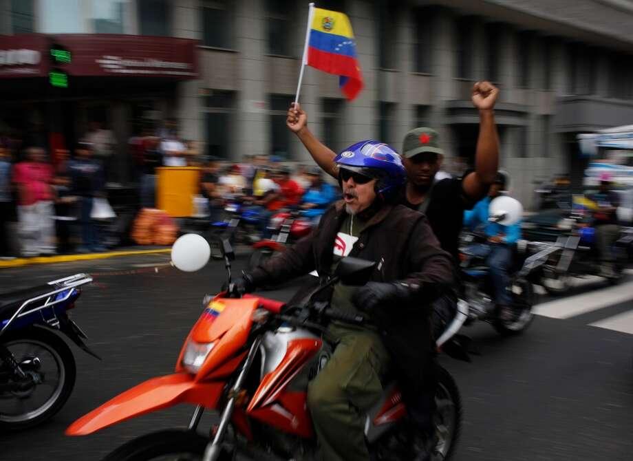 Motociclistas participan de una recorrida a favor del presidente venezolano Nicolás Maduro en Caracas el lunes 24 de febrero de 2014. La capital venezolana amaneció el lunes en medio de nuevas tensiones luego de que decenas de manifestantes bloquearon algunas de las principales avenidas en protesta contra el gobierno, en medio de la crisis política que lleva tres semanas y ha dejado 14 muertos y más de un centenar de heridos. Photo: Rodrigo Abd, Associated Press