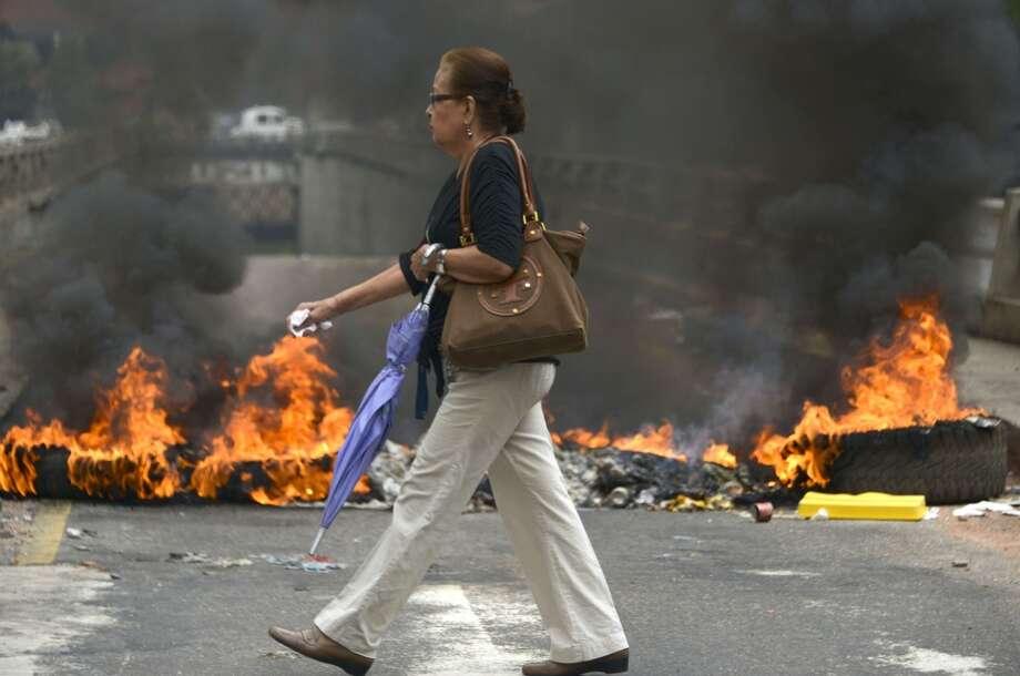 La capital venezolana amaneció el lunes en medio de nuevas tensiones luego de que decenas de manifestantes bloquearon algunas de las principales avenidas en protesta contra el gobierno, en medio de la crisis política que lleva tres semanas y ha dejado 14 muertos y más de un centenar de heridos. Photo: RAUL ARBOLEDA, AFP/Getty Images